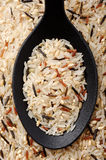 Mixed rice (Parboiled, wild, brown. Top view of black spoon full of mixed rice Stock Photos