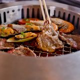 Mixed Roasted Meat and Seafood and Chopsticks on the BBQ Grill o Stock Photo