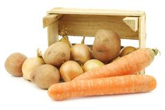 Mixed root vegetables for making `hutspot` in a wooden crate. On a white background stock photos