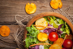 Mixed salad with croutons. Mixed salad in a wooden bowl. Selective focus stock image