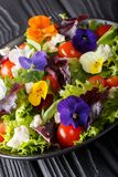 Mixed salad of edible flowers with lettuce, tomatoes and cream c. Heese close-up on the table. vertical stock photos