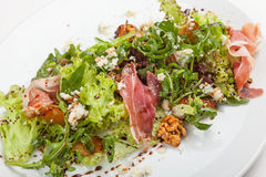 Mixed salad with herbs, prosciutto and parmesan. Stock Photos
