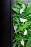 Mixed salad leaves with radish on black slate plate. Top view. Stock Photo