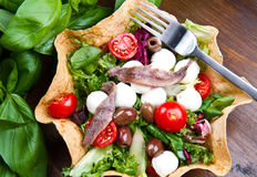 Mixed salad with mozzarella and anchovy. In a bread basket Royalty Free Stock Photos