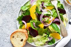 Mixed salad with orange, beetroot and sauce on the kitchen table. Organic Food. Vegan stock images