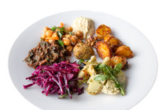 Mixed salad with red cabbage, spinach, baked potatoes, hummus, c. Hickpeas and artichokes on a white plate isolated Royalty Free Stock Images