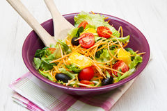 Mixed salad with tomatoes in purple bowl Stock Photos