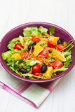 Mixed salad with tomatoes in purple bowl Royalty Free Stock Photography