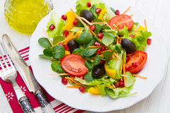 Mixed salad with tomatoes in white plate on wood table Stock Photo