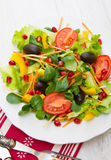 Mixed salad with tomatoes in white plate on wood table Royalty Free Stock Images