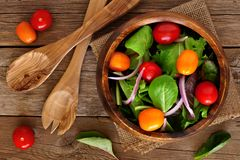 Mixed salad in wooden bowl overhead scene on rustic wood Royalty Free Stock Photography