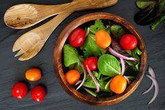 Mixed salad in wooden bowl, overhead scene on slate Royalty Free Stock Photos