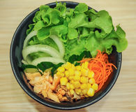 Mixed salmon salad bowl. Salmon salad in black bowl including lettuce, shredded carrot,sweet corn,onion rings, cucumber and salmon meat Royalty Free Stock Photography