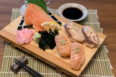 Mixed salmon sushi on wooden plate along with Japanese sauce and royalty free stock photography