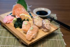 Mixed salmon sushi on wooden plate along with Japanese sauce and royalty free stock photos