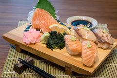 Mixed salmon sushi on wooden plate along with Japanese sauce and stock photo