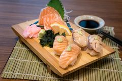 Mixed salmon sushi on wooden plate along with Japanese sauce and stock image