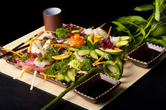 Mixed sashimi, raw fish with seaweed. Mixed sashimi, raw fish with cucumber and seaweed on traditional japanese plate. soy sauce and chopsticks stock photography