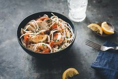 Mixed seafood bowl with pasta and lemons on a rustic background. royalty free stock photos