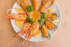 Closeup Mixed Seafood On Plate. Mixed Seafood Contain Big Shrimps, Grilled with Sauce and Lemon on Dish, Isolated on Wood background Stock Photo