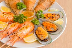Closeup Mixed Seafood On Plate. Mixed Seafood Contain Big Shrimps, Grilled with Sauce and Lemon on Dish, Isolated on Wood background Royalty Free Stock Photography