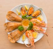 Closeup Mixed Seafood On Plate. Mixed Seafood Contain Big Shrimps, Grilled with Sauce and Lemon on Dish, Isolated on Wood background Stock Photography