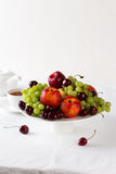 Mixed set of fresh raw ripe fruits. Apple, peach, grape and cherries on white porcelain plate isolated over white background Stock Images