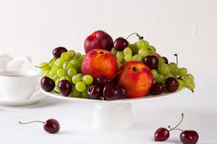 Mixed set of fresh raw ripe fruits. Apple, peach, grape and cherries on white porcelain plate isolated over white background Royalty Free Stock Image