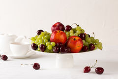 Mixed set of fresh raw ripe fruits. Apple, peach, grape and cherries on white porcelain plate isolated over white background Royalty Free Stock Photography