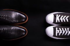 Mixed shoes. Oxford and sneakers shoe on black background.  Different style of men fashion. Compare  formal  casual. Top view. Cop Royalty Free Stock Images