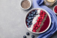 Mixed smoothie bowl raspberry blueberry chia seeds. Mixed smoothie bowl with fresh raspberry, blueberry, coconut flakes and chia seeds. Grey stone background Stock Images