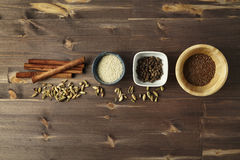 Mixed spice. Cardamom, cinnamon, anise, allspice, sesame seeds i. N bowls on wooden table royalty free stock photography