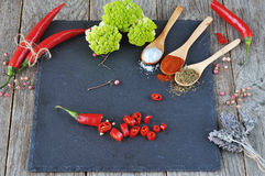 Mixed spices and Condiments  on  the stone, slate and wooden background. Hot peppers and cauliflower. Salt, red pepper. black pepper, a bunch of lavender Royalty Free Stock Photography