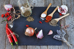 Mixed spices and Condiments  on  the stone, slate and wooden background. Hot peppers and garlic,. Salt, red pepper. black pepper, a bunch of lavender Stock Photos
