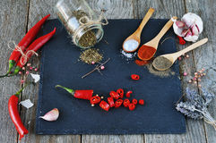 Mixed spices and Condiments  on  the stone, slate and wooden background. Hot peppers and onions. Salt, red pepper. black pepper, a bunch of lavender Royalty Free Stock Photos