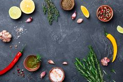 Mixed spices and herbs on black stone table top view. Ingredients for cooking. Food background. Mixed spices and herbs on black stone table from above stock images