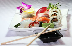 Mixed Sushi Plate. A plate of mixed sushi with crossed chopsticks laying on a sauce dish Royalty Free Stock Photo