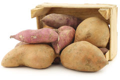 Mixed sweet potatoes in a wooden crate Stock Images