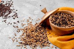 Mixed varieties of malted grain in a wooden plate on a gray background. close-up. series of photos. space. Mixed varieties of malted grain in a wooden plate on a stock image