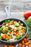 Mixed vegetable meal in old black frying pan closeup. And ingredients on wooden rustic table Royalty Free Stock Photos