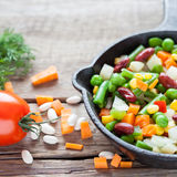 Mixed vegetable meal in old frying pan closeup and ingredients Royalty Free Stock Images