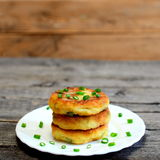 Mixed vegetable patties on a plate isolated on wooden background. Fried patties cooked of potatoes, green peas, carrot Royalty Free Stock Images
