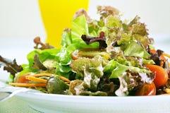 Mixed vegetable salad. Fresh vegetable salad with orange juice background Royalty Free Stock Images