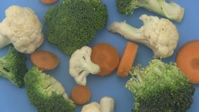 Mixed vegetables on a blue background. stock video