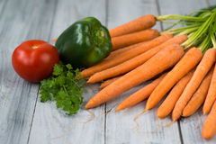 Mixed vegetables. Carrots, paprika, tomato and herbs on wooden background Royalty Free Stock Image