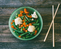 Mixed vegetables and chopsticks on the old wooden table Stock Images