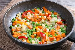 Mixed vegetables in a frying pan on wood table, Stock Image