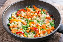 Mixed vegetables in a frying pan on wood table, Royalty Free Stock Image