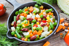 Mixed vegetables in retro frying pan and ingredients Stock Photo