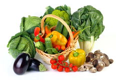 Mixed vegetables. Seasonal vegetables on white background with wicker basket Stock Photography